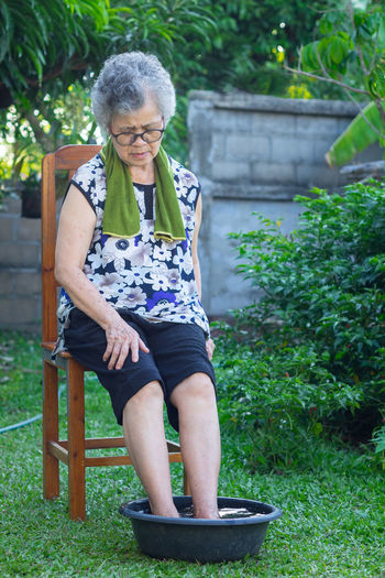 Elderly woman sitting on chair have a ankle pain and spa foot with herbs in garden