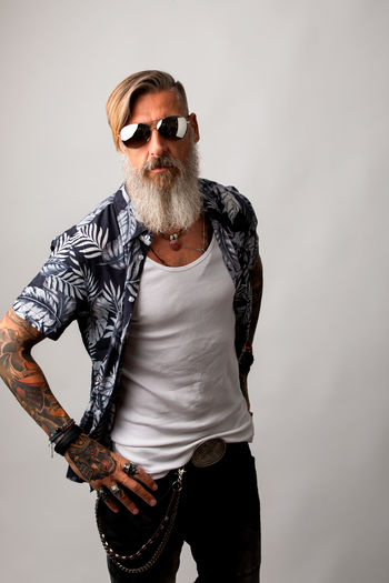Portrait of a bearded hipster isolated on a white background Studio Shot Facial Hair Beard Glasses Indoors  Front View Gray Background Casual Clothing One Person Males  Three Quarter Length Standing Sunglasses Modern Model Looking At Camera Shirt Jeans Hipster Biker Rocker Cut Out Posing Attractive Men