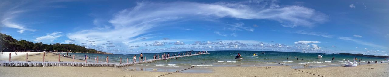 Panoramic view of people on beach against blue sky
