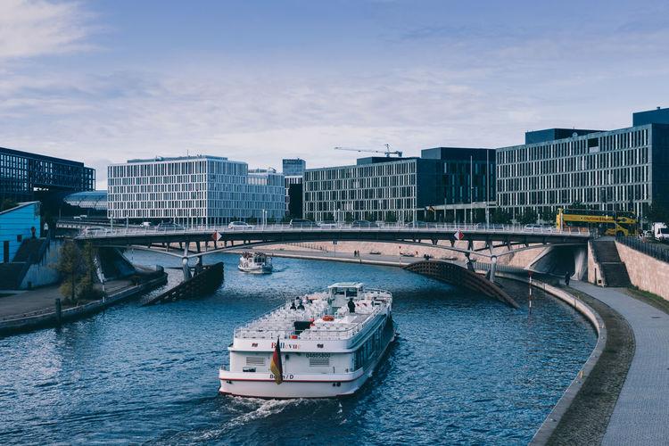 Nautical vessel on bridge in city against sky