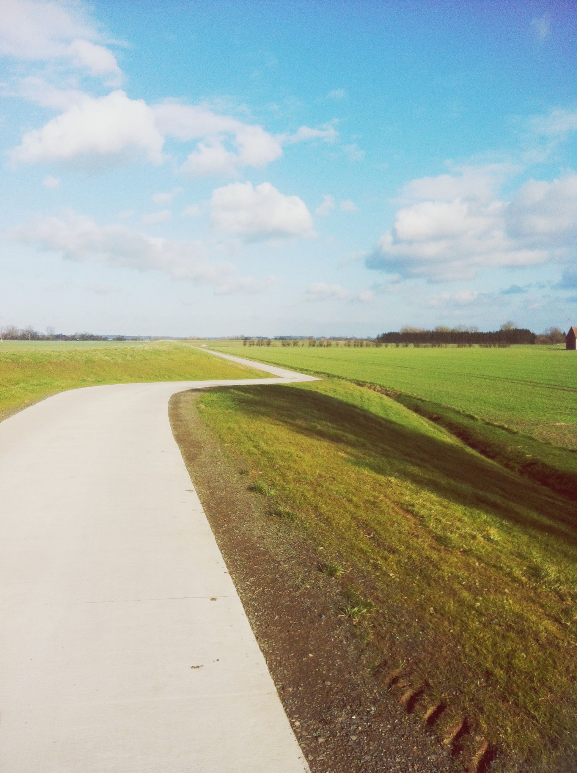sky, landscape, grass, tranquil scene, tranquility, field, the way forward, scenics, rural scene, cloud - sky, nature, beauty in nature, road, cloud, agriculture, green color, diminishing perspective, horizon over land, dirt road, vanishing point