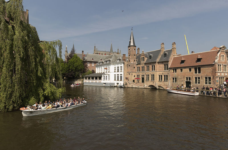 Bruges, Belgium May 9, 2018: Views of a canal in the city of Bruges with tourists taking a boat ride. Belgium Architecture Belgian  Bruges Building Exterior Built Structure City Crowd Day Europe Group Of People Large Group Of People Mode Of Transportation Nature Nautical Vessel Outdoors Passenger Craft Real People River Transportation Travel Tree Water Waterfront Women