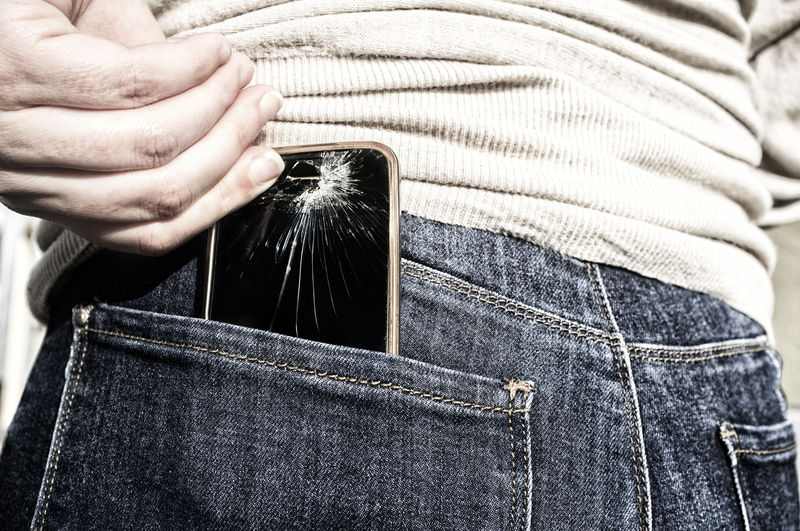 Close-up of person removing broken smart phone from pant back pocket
