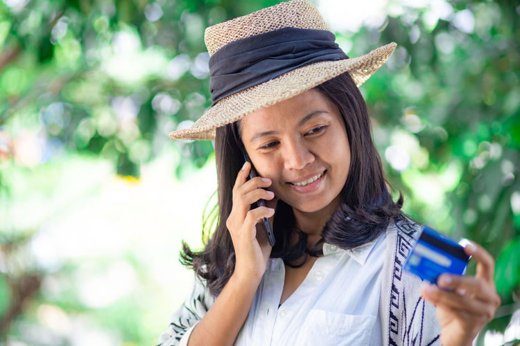 Mid adult woman with credit card talking over mobile phone while standing against trees