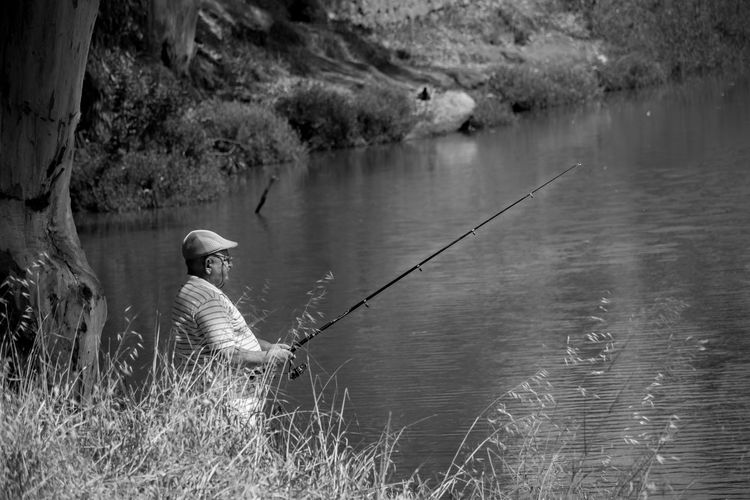 Side view of senior man fishing in lake