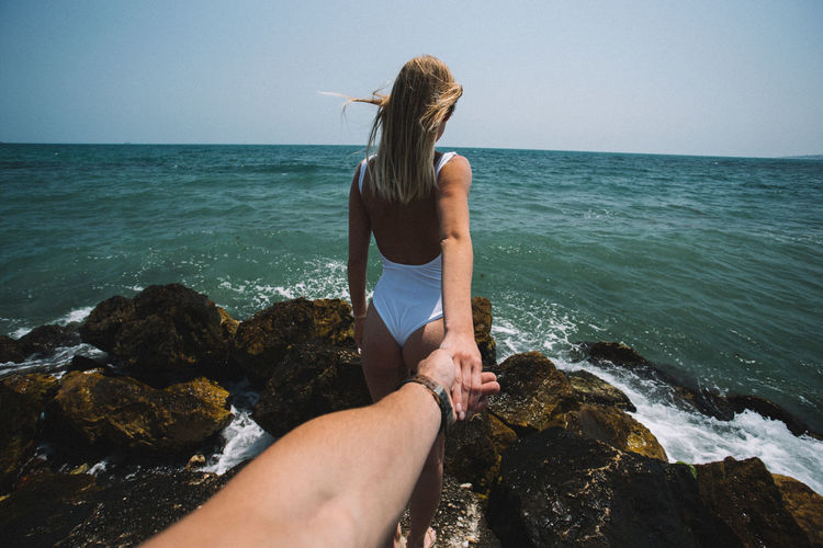Rear view of woman holding hand of boyfriend by sea on rock
