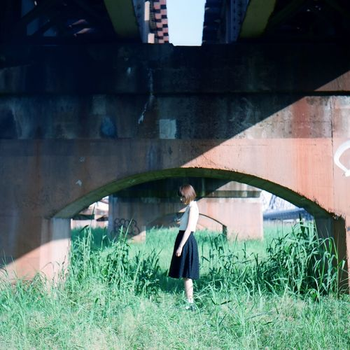 Side View Of Woman Standing Under Bridge