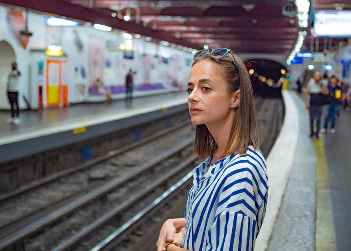 Woman looking away while standing at railroad station