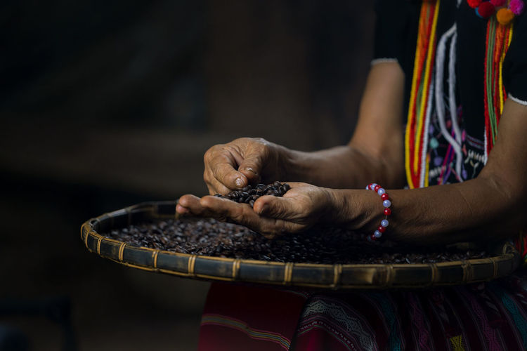 Hill tribe women sorting coffee beans. woman selecting roasted coffee bean. thailand.