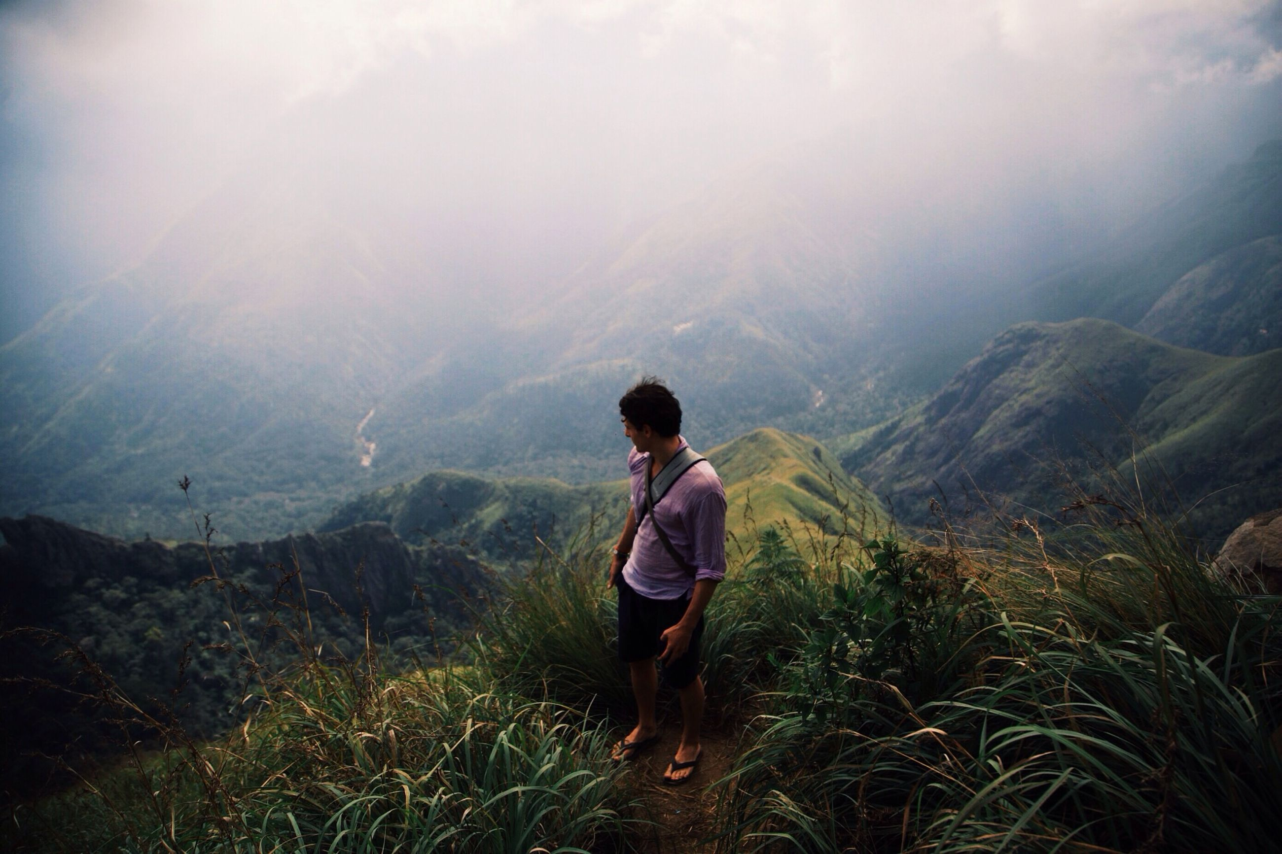 mountain, tranquil scene, tranquility, scenics, rear view, beauty in nature, mountain range, landscape, lifestyles, leisure activity, nature, sky, full length, standing, non-urban scene, casual clothing, getting away from it all, remote