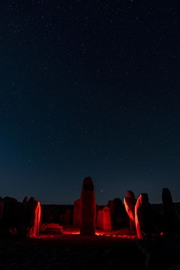 People on rock formations against sky at night