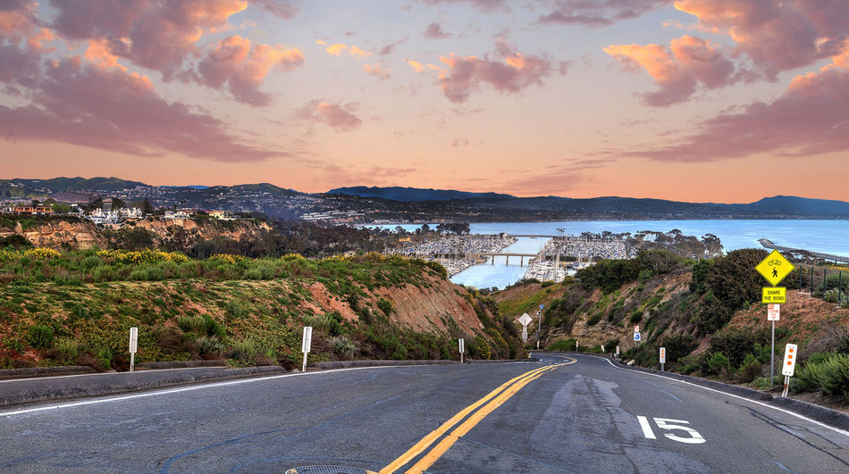 Road leading down to Dana Point Harbor at sunset in Southern California, USA Adventure California Dana Point Harbor Dana Point, Ca Drive Harbor Harbor View Journey Nature Ocean Ocean View Orange County, Ca Pink Sunset Road Sea Sky Sky And Clouds Street Sunset Travel