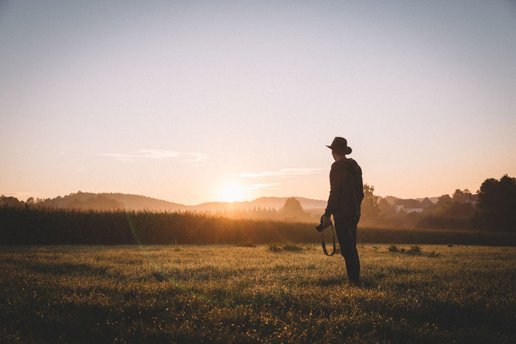 Rear view photographer standing on field during sunrise