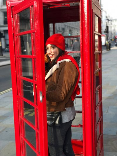 Red Hat Clothing One Person Standing Knit Hat Architecture Young Adult Young Women Warm Clothing Looking At Camera Winter Portrait Adult Smiling Lifestyles Women Telephone Booth Real People Beautiful Woman