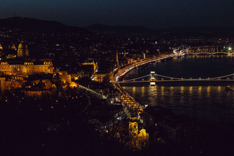 High angle view of illuminated bridge over river in city at night