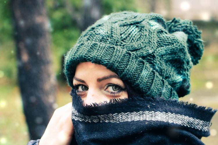Close-up portrait of woman wearing knit hat standing outdoors