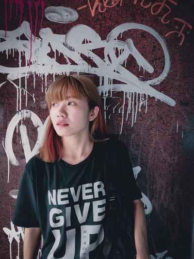 Young woman against graffiti wall