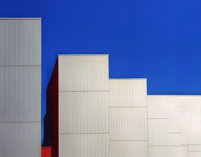 Close-up of white building against blue sky