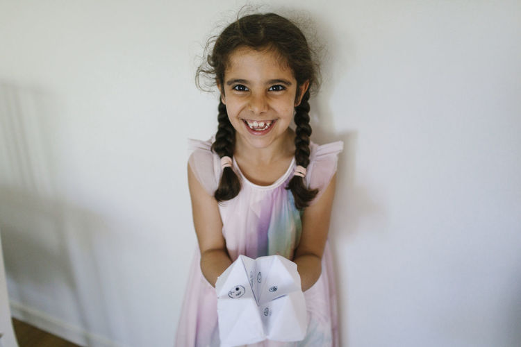Portrait of a smiling girl standing against wall