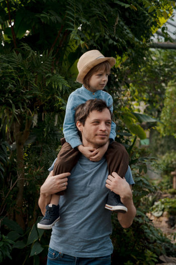 Dad and son inspecting tropical gallery in botanical garden. local travel and tourism.