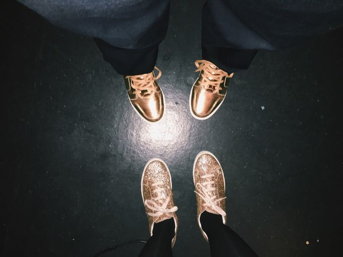 Low section of man and woman with golden shoes on floor