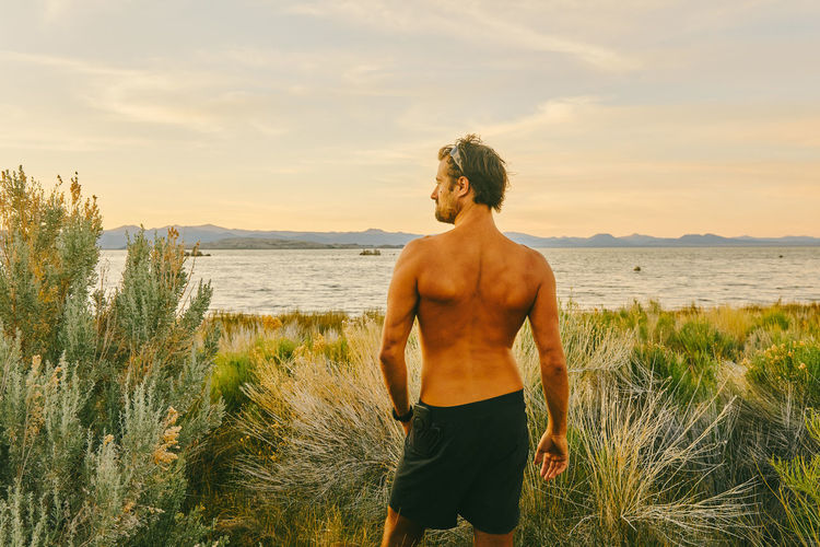 Full length of shirtless man standing at beach against sky