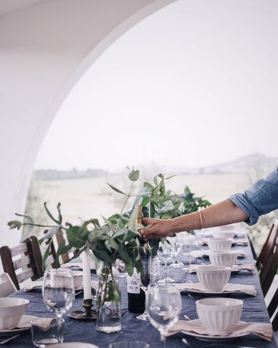Cropped hand of man table setting outdoors