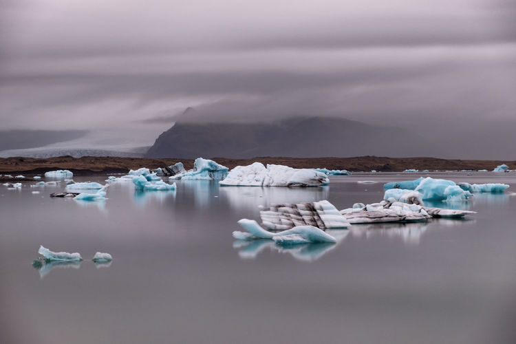 Scenic view of icebergs in sea against cloudy sky