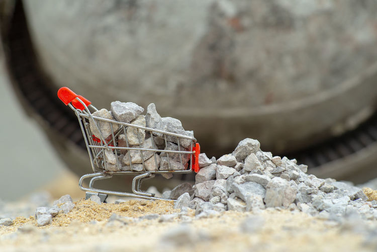 Selective focus on shopping trolley carries the crushed stones and pouring onto the pile at the construction site Selective Focus Outdoors Abundance Concrete Trolley Shopping Cart Toy Crushed Stone