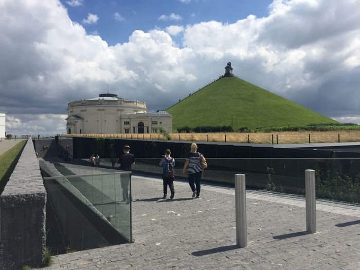 Tourist walking on street by lion mound against cloudy sky