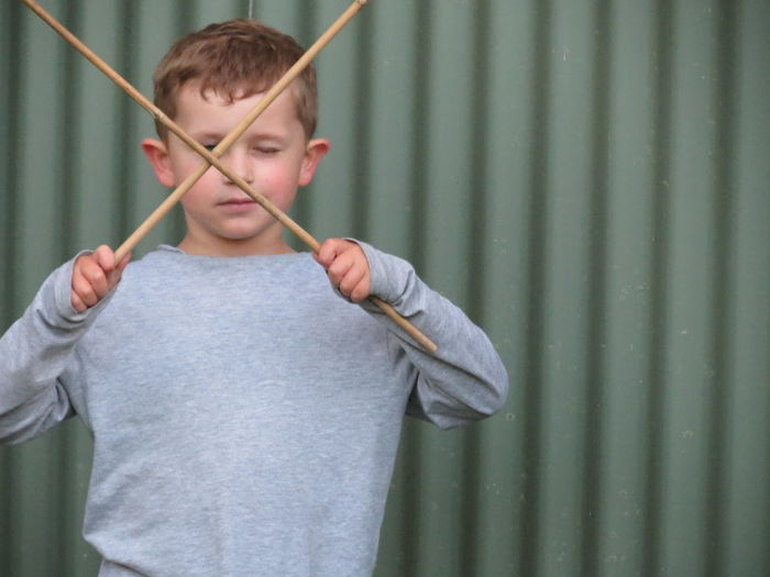 Boy Holding Sticks While Standing Against Corrugated Iron