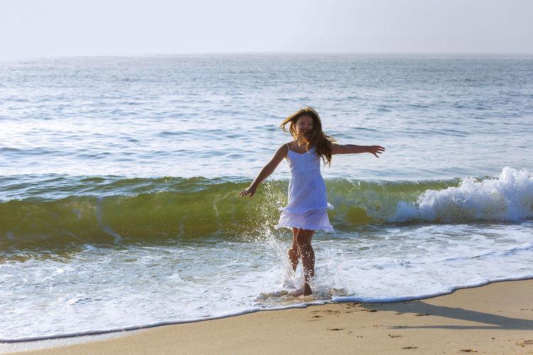 Full length of teenage girl kicking water at beach