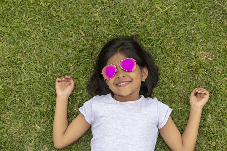 Beautiful girl with sunglasses lying on the grass Grass Leisure Activity Plant Child Front View Portrait Childhood One Person Casual Clothing Girls Smiling Day Lying Down Women High Angle View Happiness Field Green Color Females Real People Outdoors Innocence Hairstyle