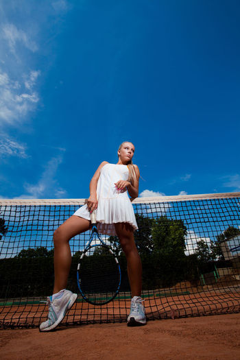 Athletic young woman in a tennis suit and racket in her hand standing in front the net. Bottom view Outdoors Women Playing Day Blue Real People Adult Ball Sky Net - Sports Equipment Lifestyles Tennis Racket Full Length Court One Person Leisure Activity Tennis Racket Sport Skill