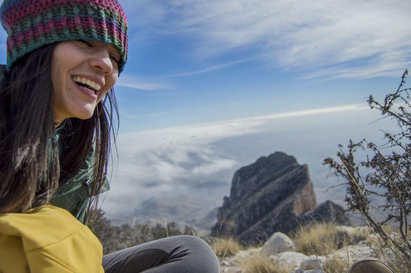 Woman sitting on rock against cloudscape