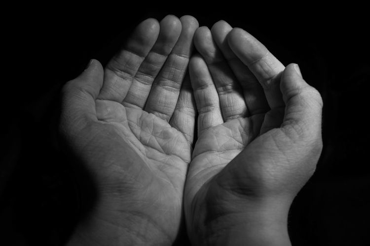 Close-up of human hand praying against black background