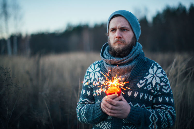 Thoughtful man holding sparkler while standing on field