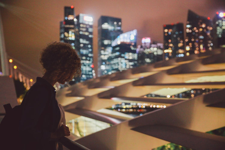 Woman Standing At Railing Against Illuminated City At Night