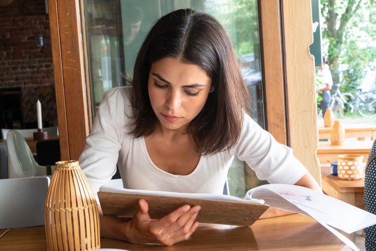 Woman reading menu while sitting on restaurant table
