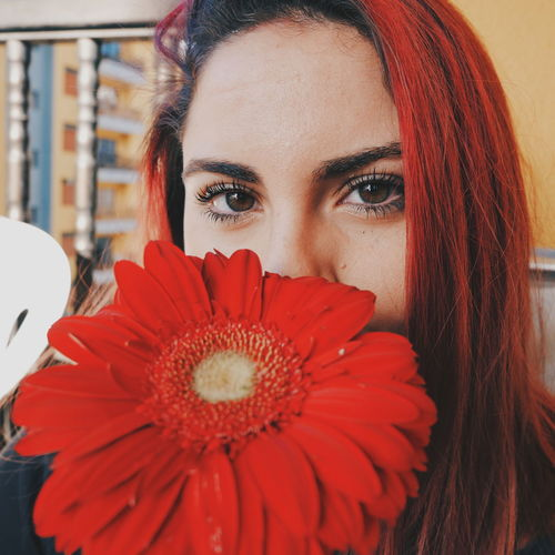 Close-Up Portrait Of Young Woman With Red Gerbera Daisy