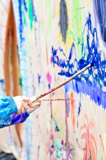 Art And Craft Artist Brush Creativity Focus On Foreground Hand Holding Human Body Part Human Hand Leisure Activity Lifestyles Multi Colored Occupation One Person Paint Paintbrush Real People Skill  Stick - Plant Part Wall - Building Feature