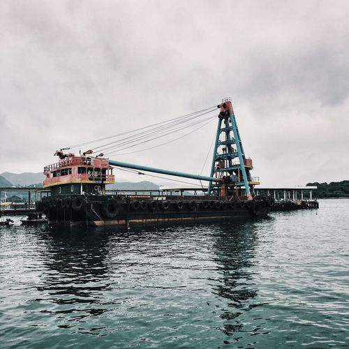 Low angle view of tugboat sailing in sea against cloudy sky