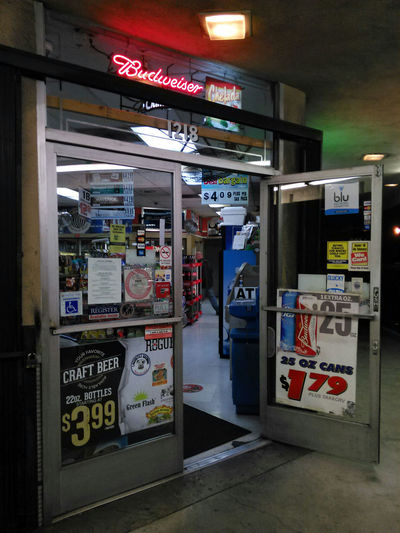 The entrance of the cleverly named Beach Ball Liquor, at the corner of Beach Blvd and Ball Road in Anaheim California . Nothing remarkable here, just the usual glorious assault on the eyes here as products and signage jostle for your attention.....and money. Liquor Store Liquor Booze Spirits Convenience Store Signage Neon Sign Chaotic Visual Merchandising Not Pretty Beer Rum Champagne Vodka Whiskey Great Selection GIN Tequila Lotto Smokes Cigarettes Junk Food Libations