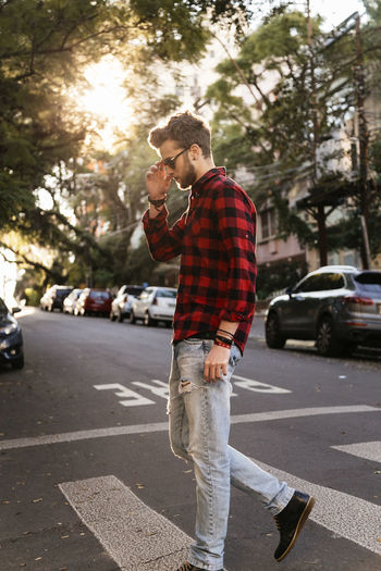 Adult Adults Only Beard Car Casual Clothing Checked Pattern City City Life City Street Day Full Length Men One Man Only One Person Only Men Outdoors People Road Standing Street Tree Walking Wireless Technology Young Adult