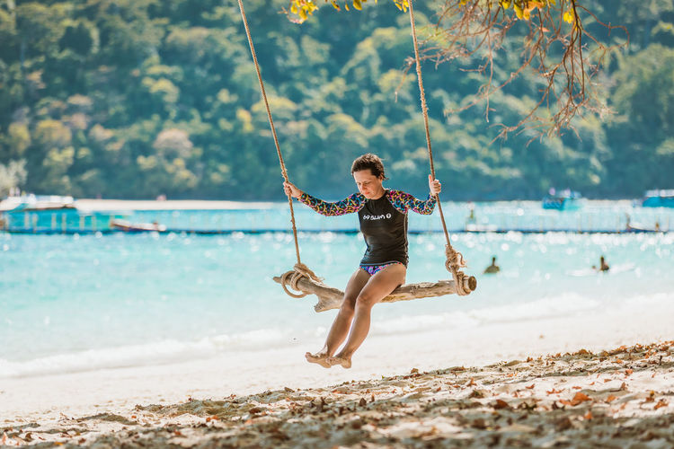 Land Water Beach Full Length Real People Sea Day One Person Leisure Activity Nature Sand Swing Focus On Foreground Tree Lifestyles Incidental People Enjoyment Fun Rope Swing Outdoors My Best Photo