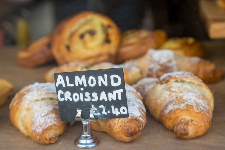 Croissants for sale in a shop window, with a shallow depth of field Food Food And Drink Freshness Baked French Food Bread Indoors  Close-up Text Still Life No People Bakery Croissant Western Script Sweet Food Store Baked Pastry Item Focus On Foreground Table Sign For Sale