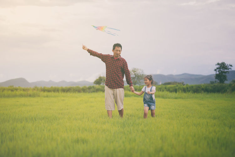 Father with daughter holding kite walking on grassy field against sky