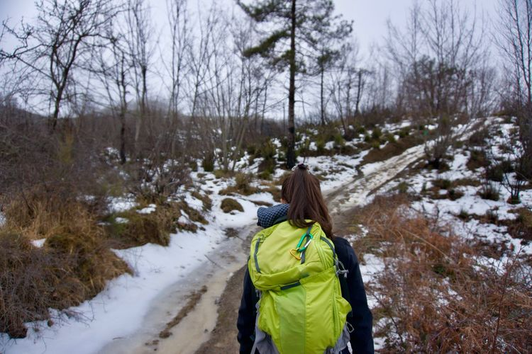 Backpacker walking on snowy field against bare trees