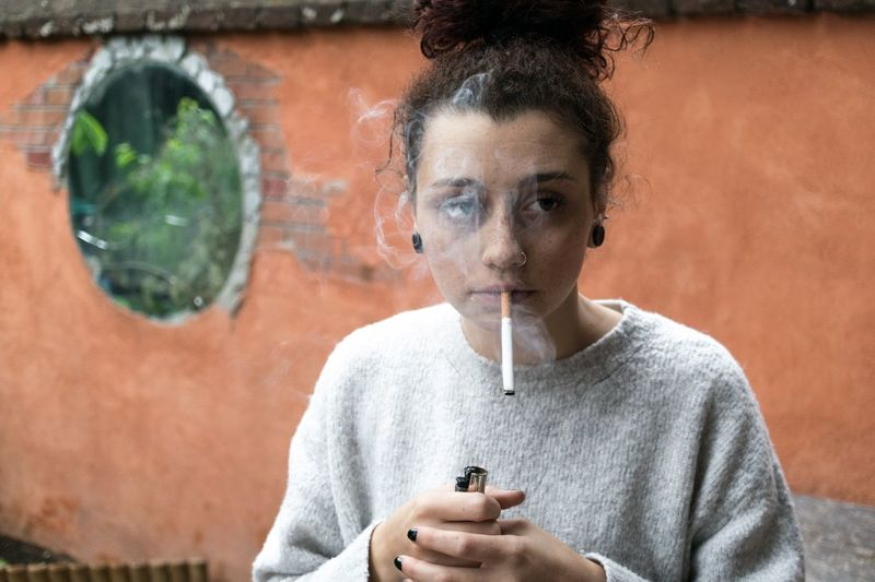 Young woman smoking while standing against wall