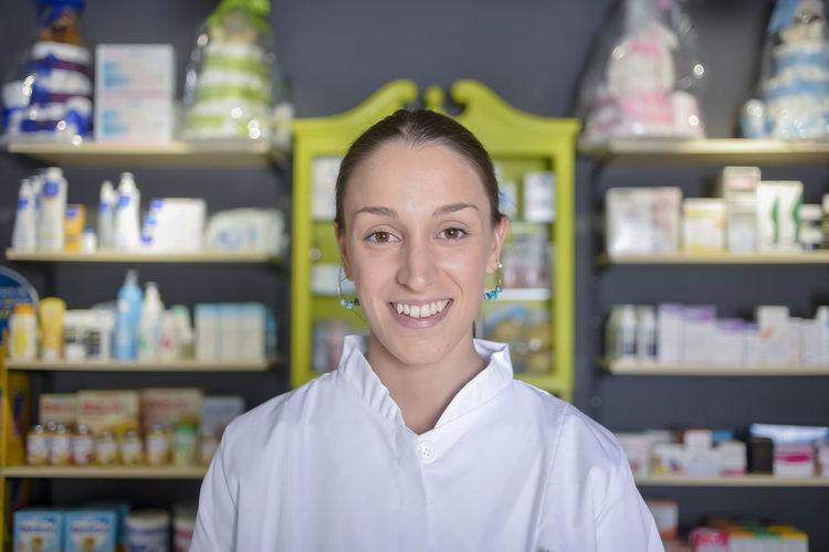 Portrait Of Female Pharmacist Standing Against Shelf In Store